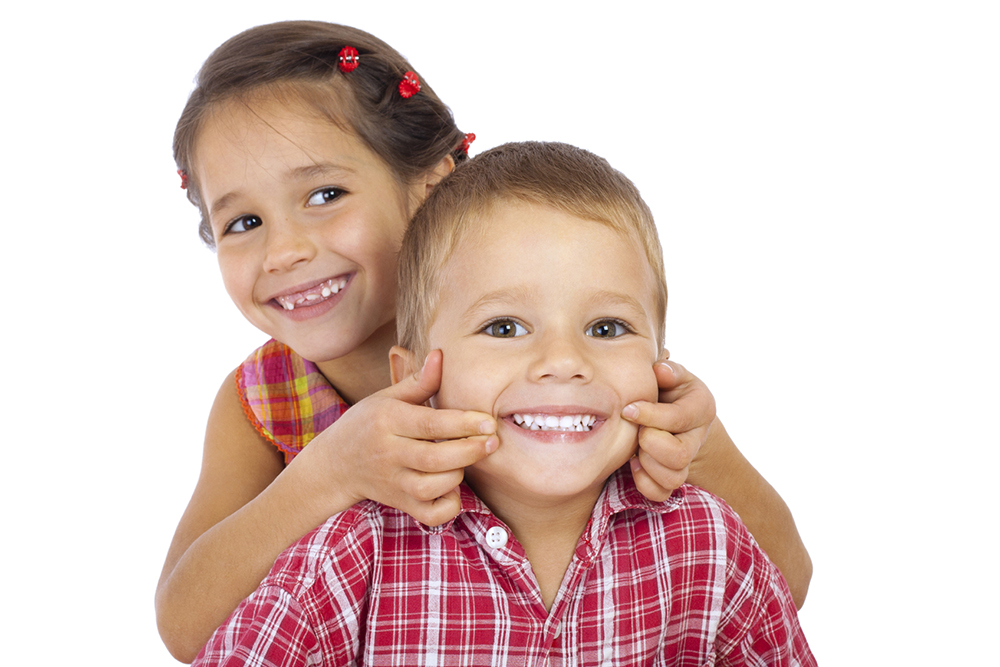 Two funny smiling little children, showing their teeth, isolated on white